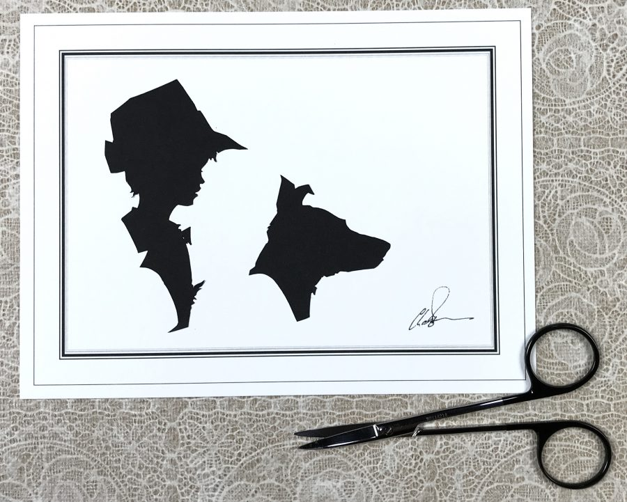 Silhouettes of a boy and dod on a white card with a pair of scissors