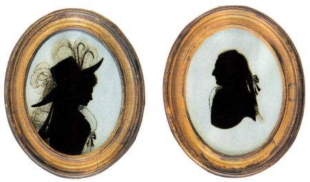Silhouettes on a man and woman in gold oval frames. The woman has a large feathered hat.