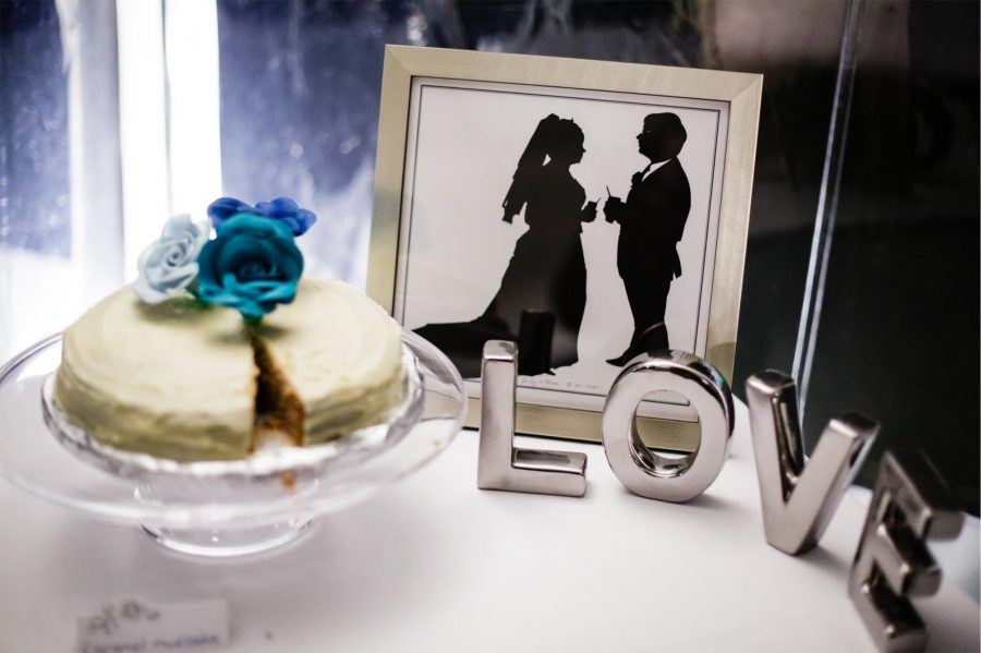 """Silhouettes of a bride and groom next to a cake and the work """"LOVE"""": wedding memories"""