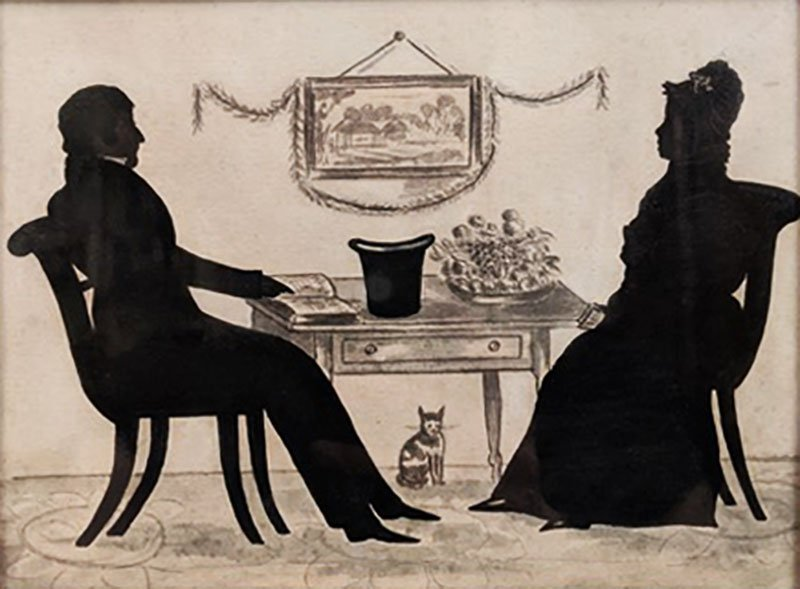 Silhouette of a man and woman facing each other across a table