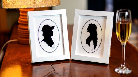 Two silhouettes in white frames next to a glass of champagne