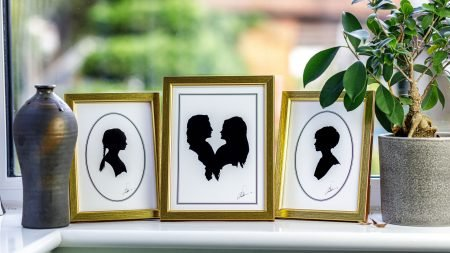 Three silhouettes on a window ledge in gold frames